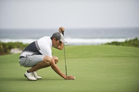 A golfer tees up his ball