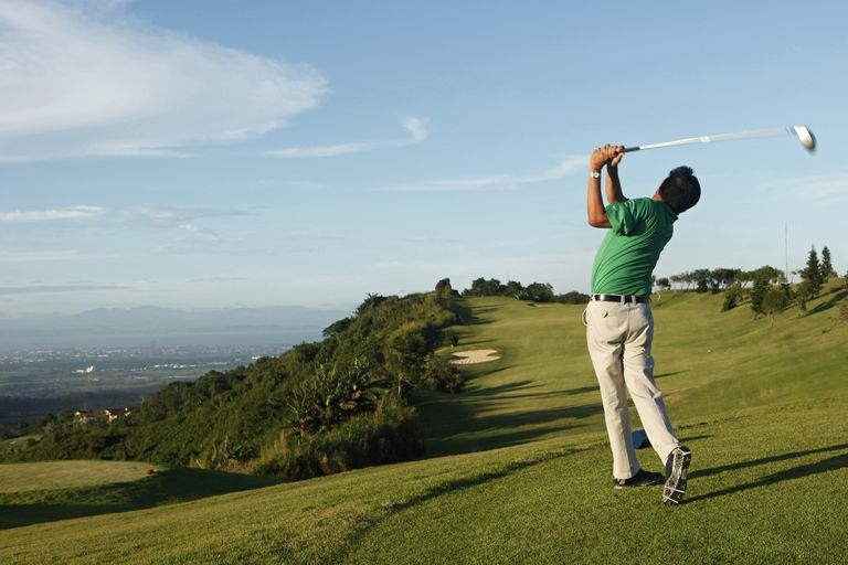 Golfer tees off, viewed from behind