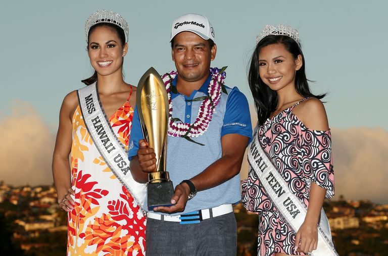 Fabian Gomez of Argentina celebrates with the winner's trophy, Miss Hawaii USA and Miss Hawaii Teen USA after defeating Brandt Snedeker during a playoff during the final round of the 2016 Sony Open