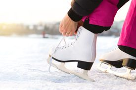 Woman tying ice skates laces by a lake or pond. Lacing iceskates. Skater about to exercise on an outdoor track or rink.