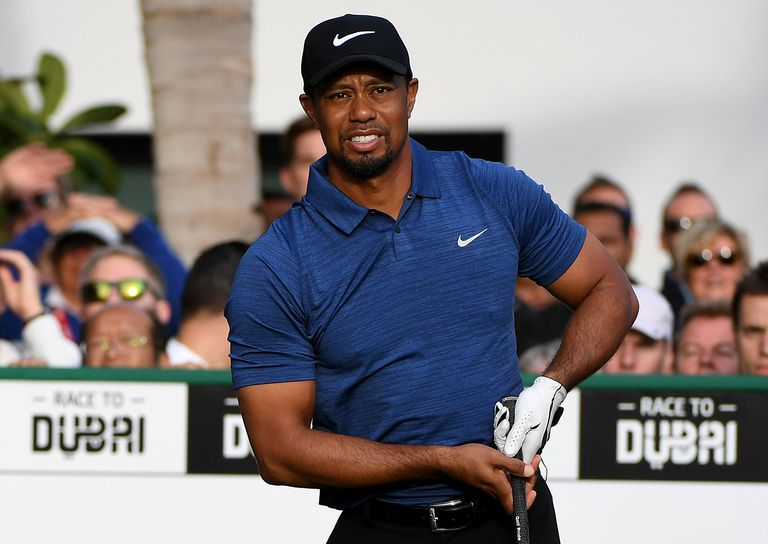 Tiger Woods o f the USA watches his tee shot on the 1st tee during the first round of the Omega Dubai Desert Classic.