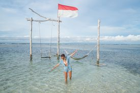Young woman walking by the sea, beautiful and idyllic landscape.