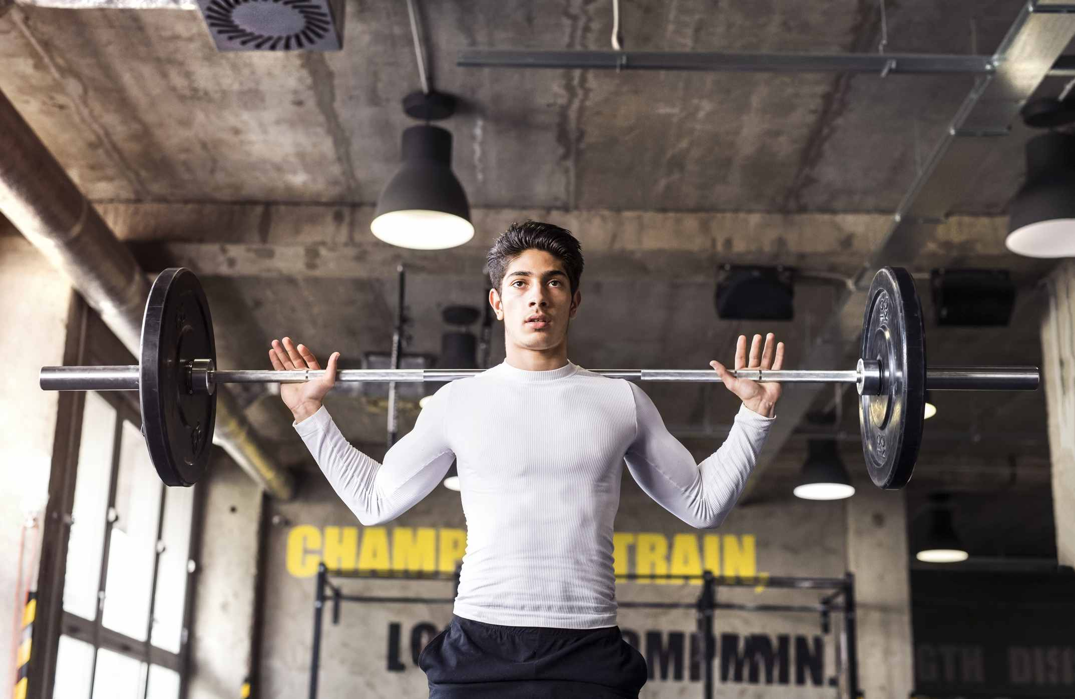 Young athlete lifting barbell in gym
