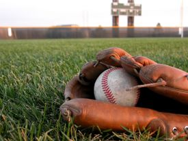 baseball glove and ball in the grass