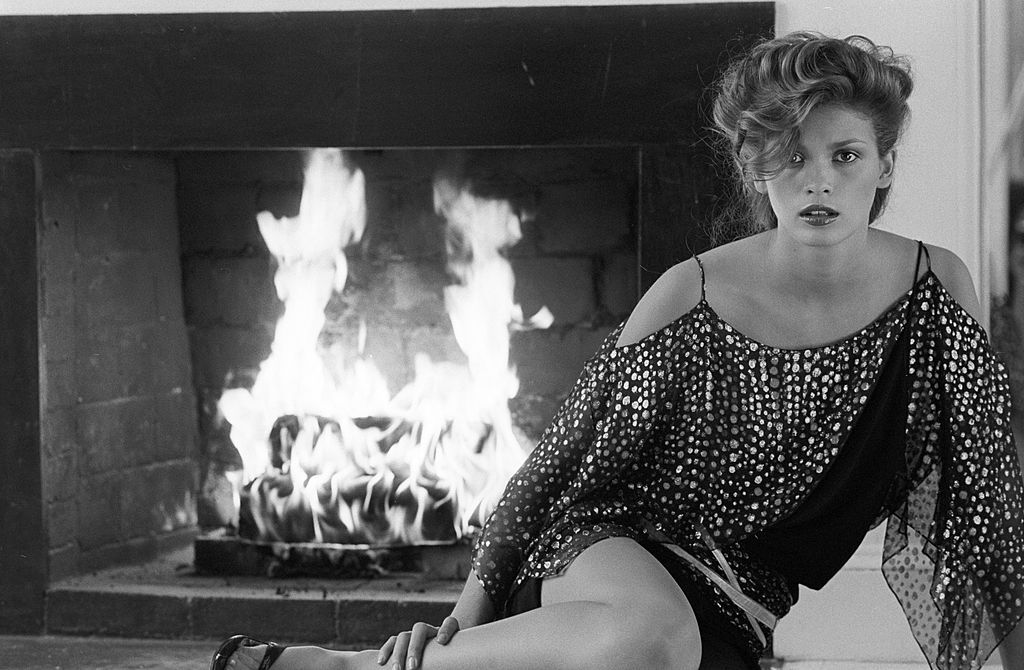 Model Gia Carangi posing in front of a fireplace