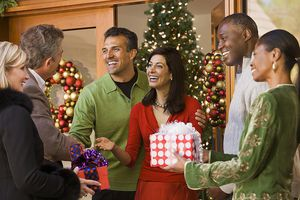Mature couple greeting guests at Christmas party, smiling