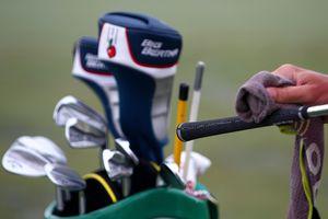 A caddie wipes down the grip on a golf club