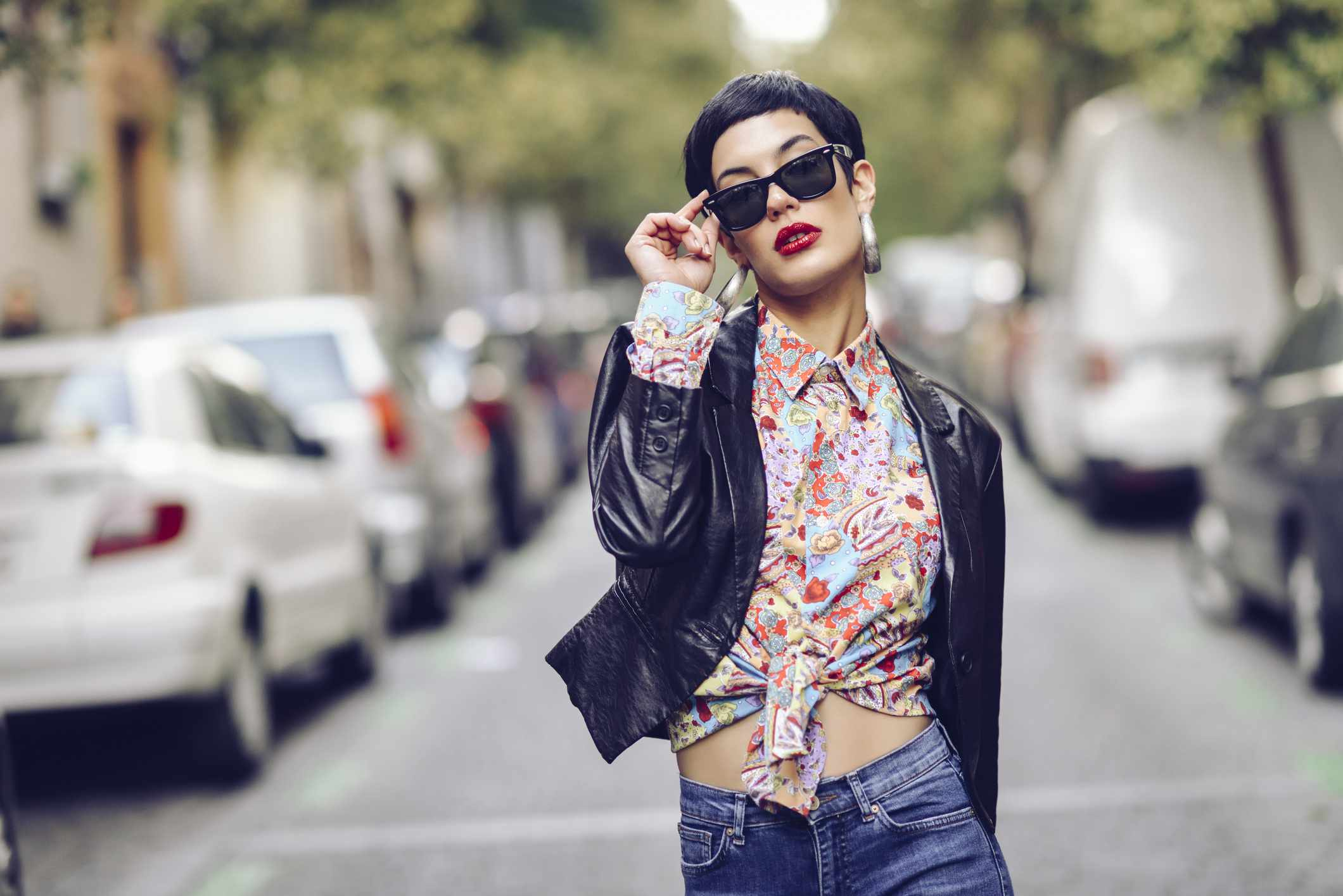 confident fashionable young woman wearing sunglasses and leather jacket