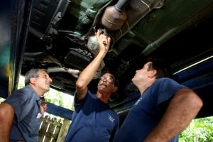 Workers inspecting an exhaust system