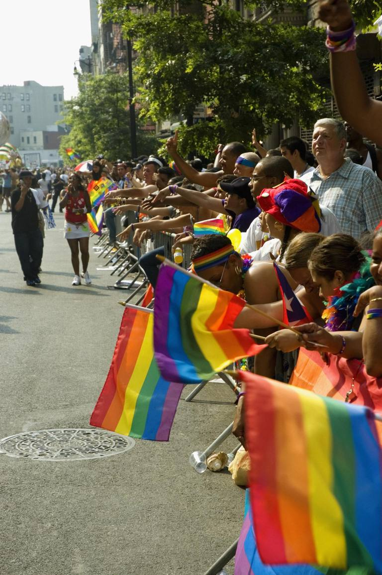 Large group of people waving gay right flags at a gay parade