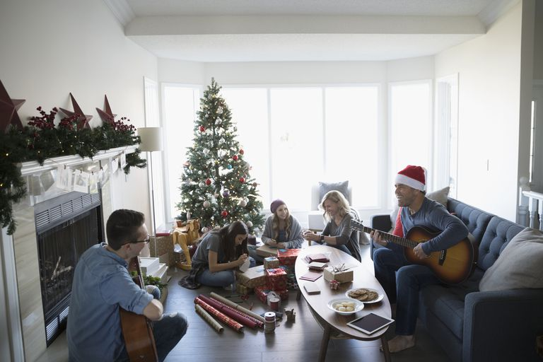 Family playing guitars and wrapping Christmas gifts in living room with Christmas tree