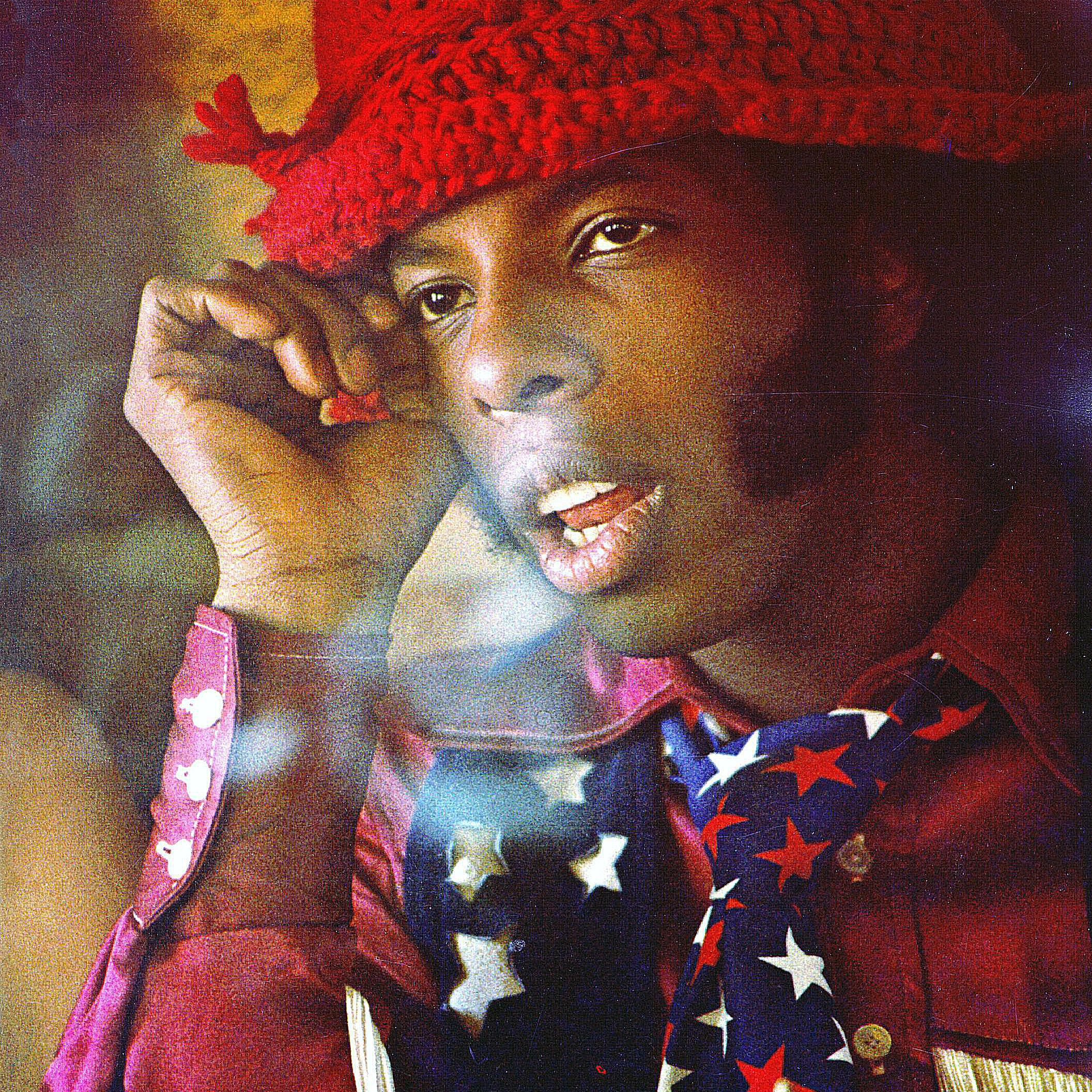 Portrait of Sylvester Stewart in a red hat.