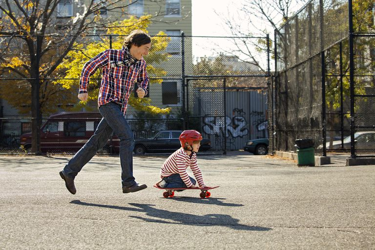 Father running beside his son as he plays on a skateboard