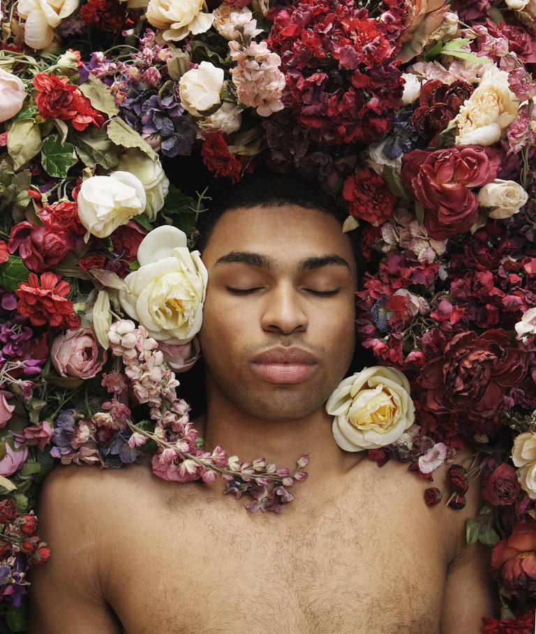 Young man lying in flowers, eyes closed, overhead view