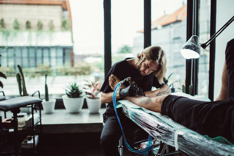 Blonde male tattoo artist tattooing the leg of a client in a well-lit shop