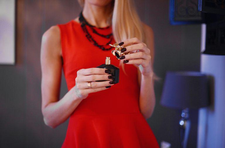 woman opening perfume bottle
