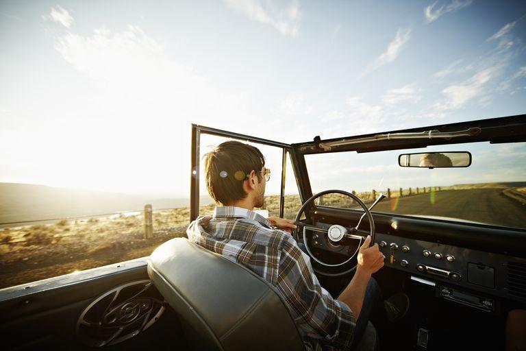 Man driving convertible on desert road at sunset