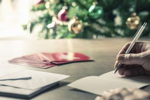 writing cards with Christmas tree in background