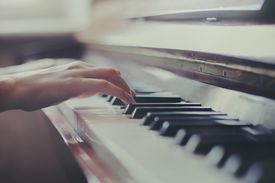 a person's hands placed on piano keys
