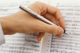 Hand holding pen writing music