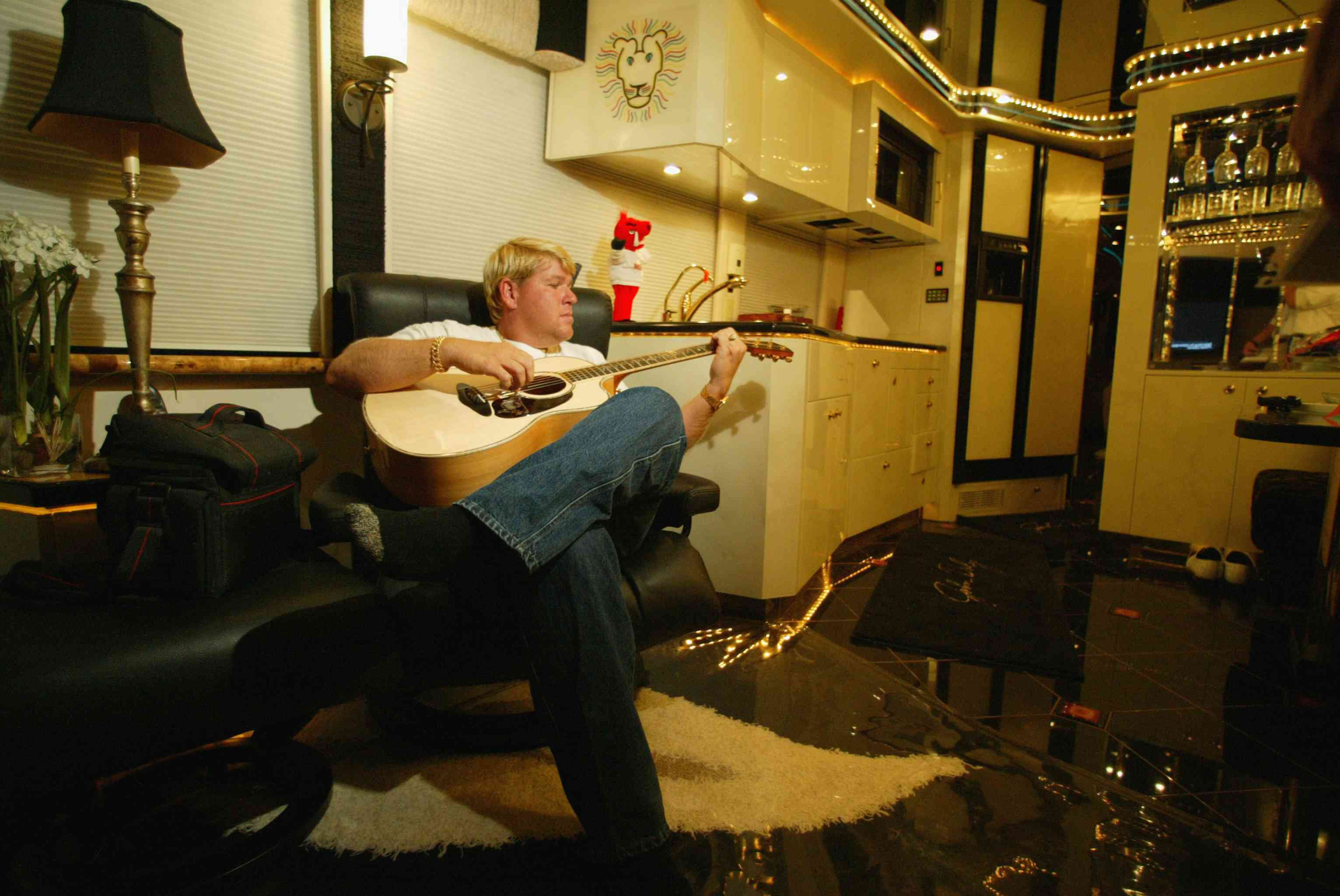 John Daly relaxes as he plays his guitar in his motorhome prior to the start of the U.S. Open on June 12, 2002 in Farmingdale, New York.