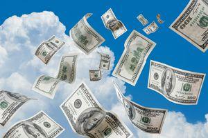 Falling money against a blue sky