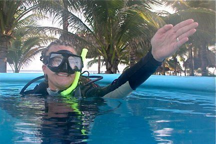 Natalie Novak in scuba gear above water pointing arm for orientation