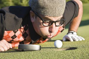 golfer trying to blow ball into hole