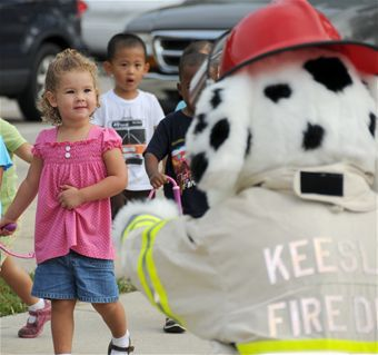 Children interacting with Keesler fire dog mascot