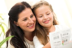 Woman and child clipping coupons