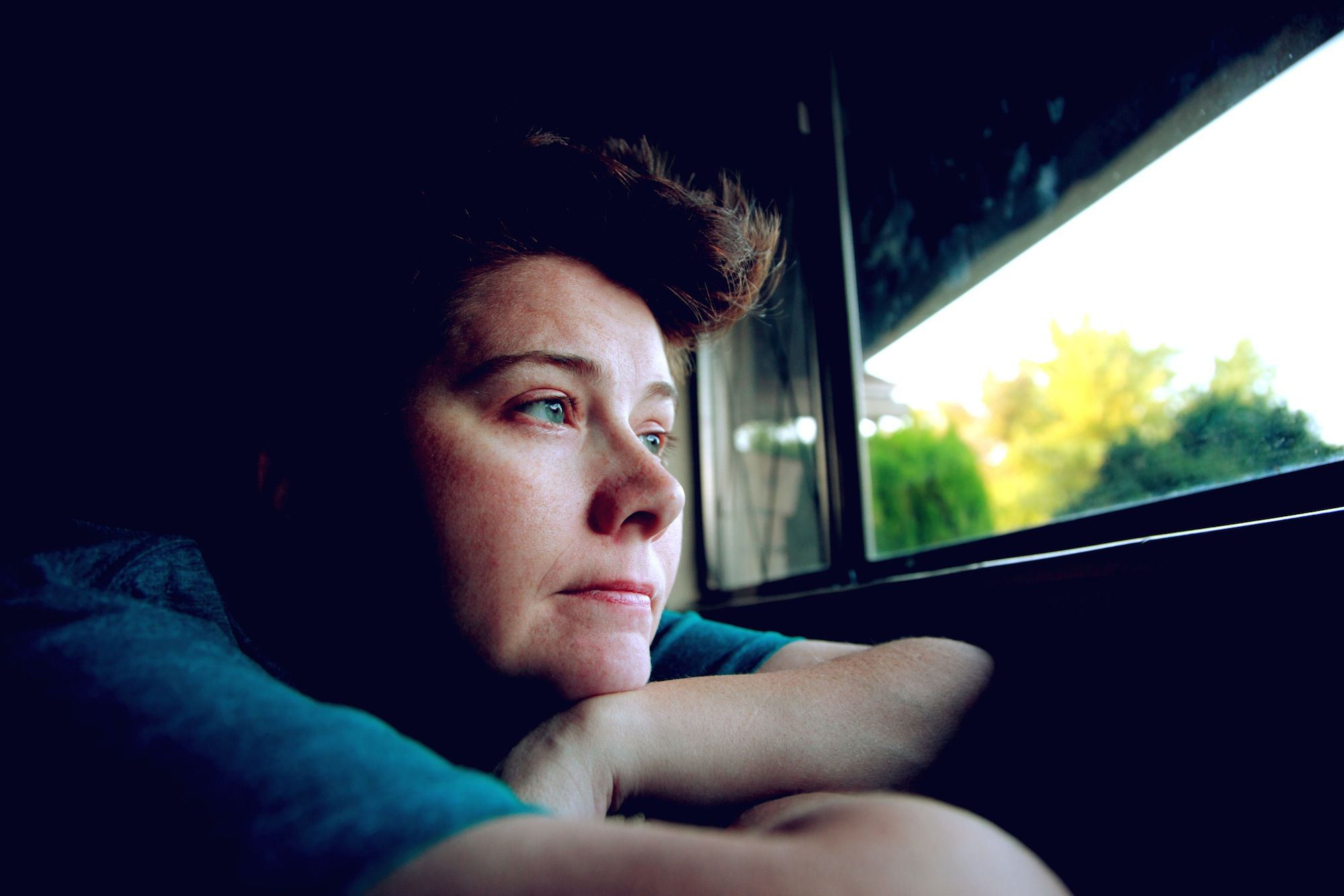 Mid Adult Woman Looking Through Window At Home