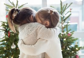 Little girls hugging in front of Christmas trees