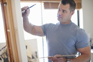 Male artist painting on an easel.