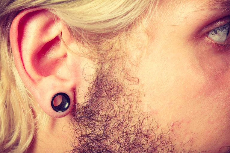 Pierced man ear, black plug tunnel