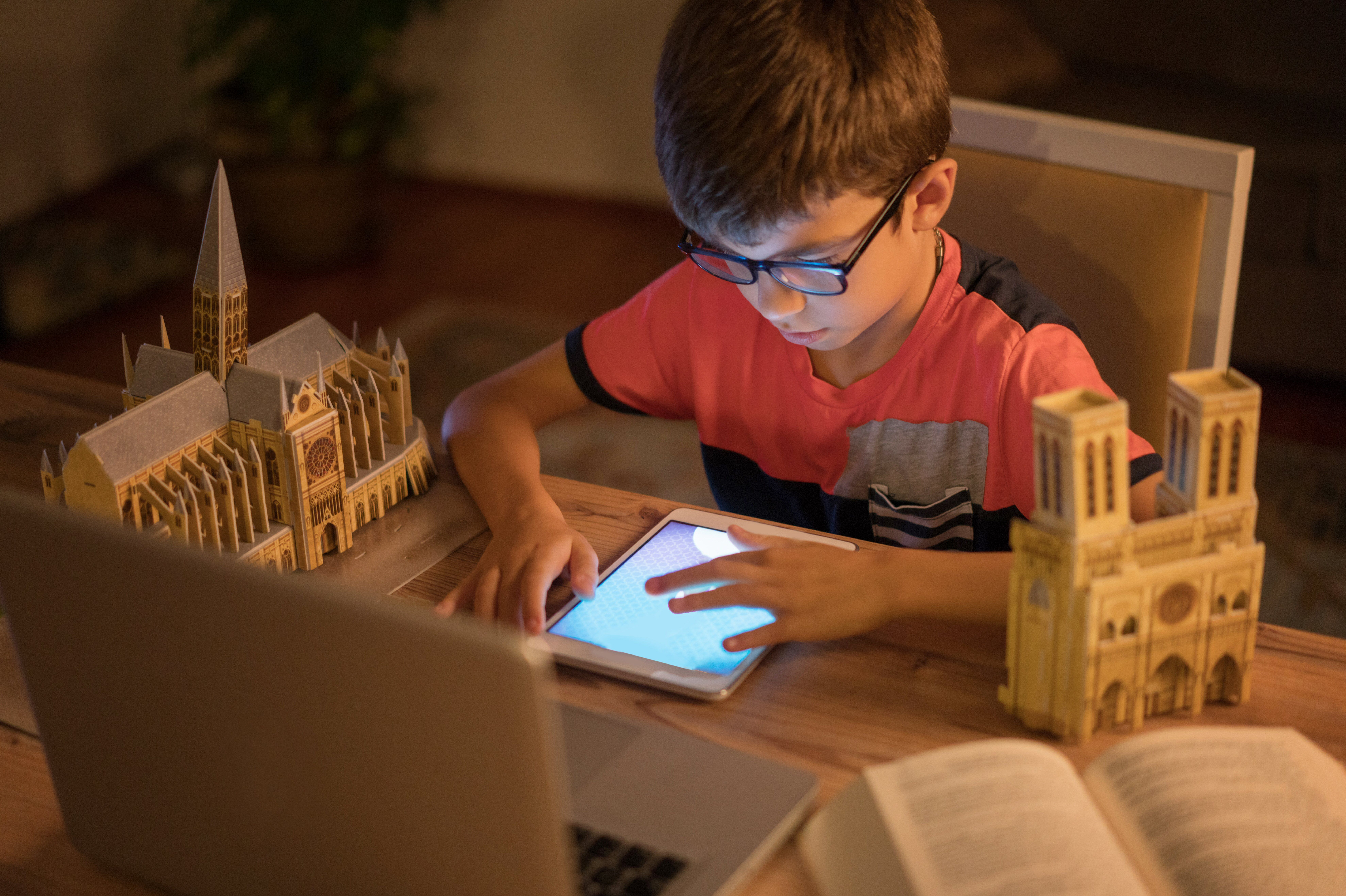 young boy with glasses sitting at table with tablet surrounded by models of buildings