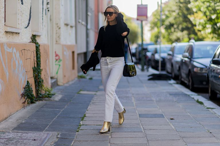 b51f2b6a920 Woman wearing white jeans black sweater and gold ankle boots