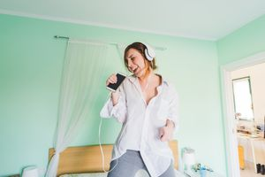 Young woman on bed wearing headphones and singing into smartphone