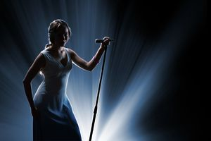 Woman onstage holding microphone on a stand, backlit