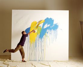Artist throwing paint at canvas