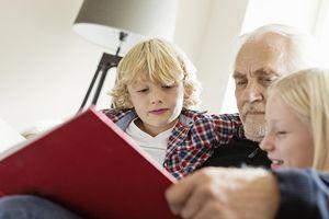 German grandfather reading book to grandchildren