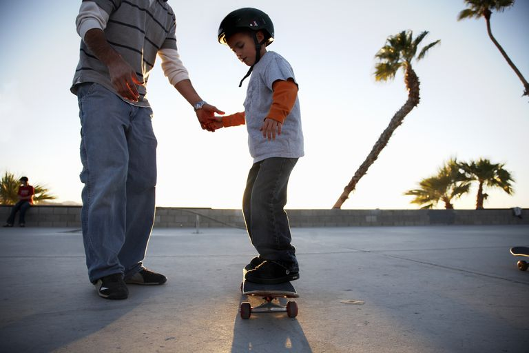 Father teaching son (10-11) skateboard
