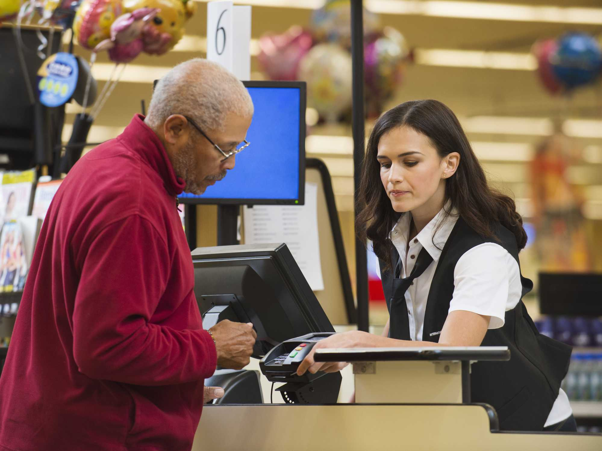 senior man checking out at store register