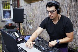 A DJ playing music in a backyard