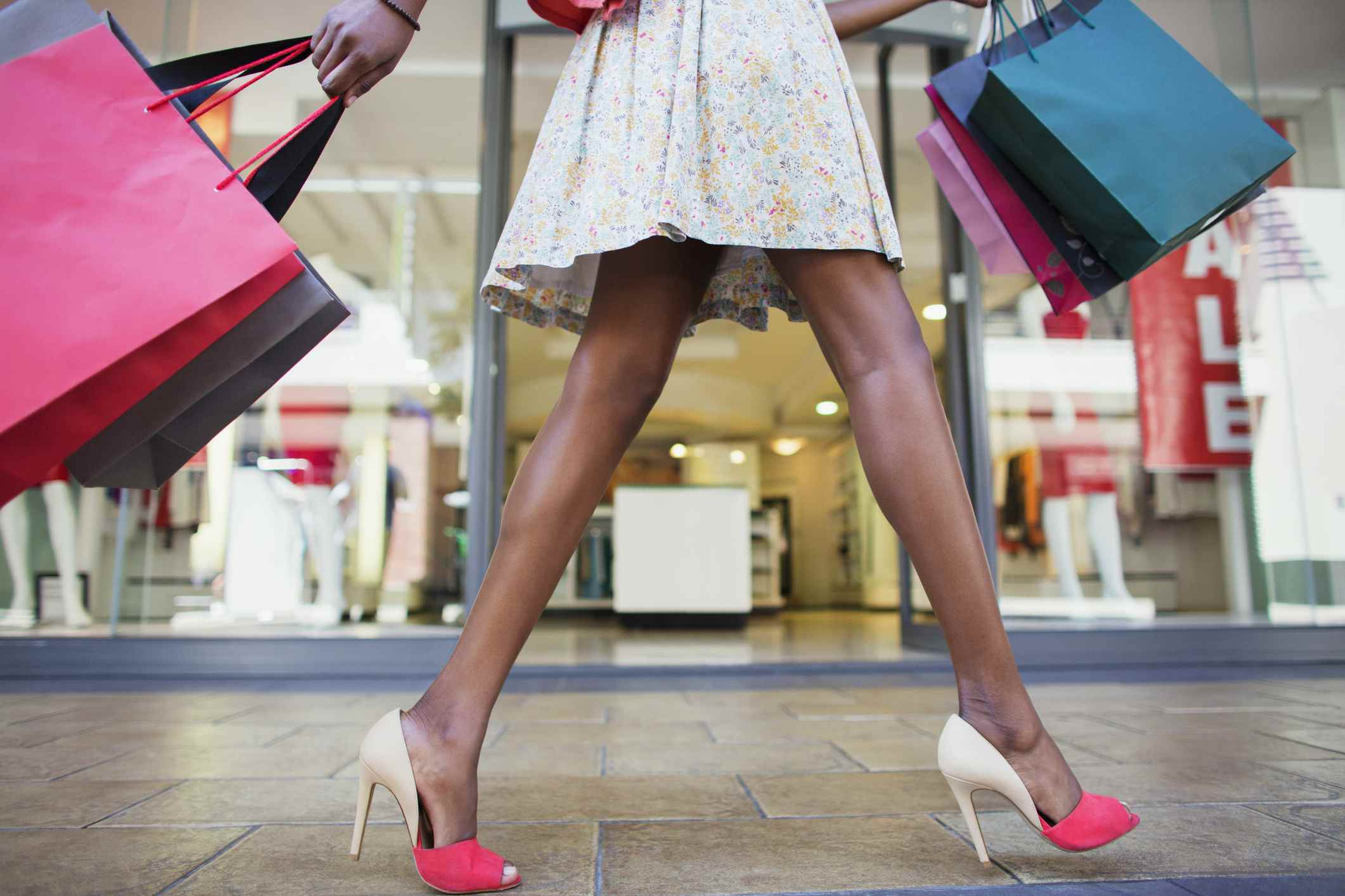 Woman with shopping bags wearing a pair of designer high heels