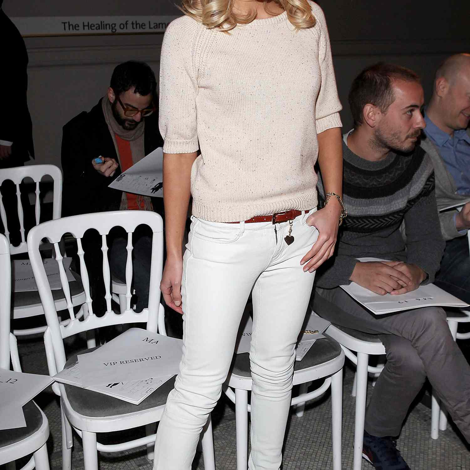 Mollie King, wearing white jeans with brown boots, and a cream sweater.