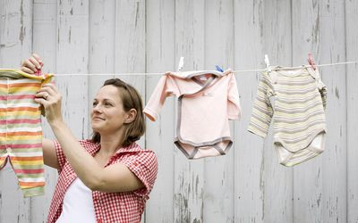 0f85a0aaac05 Pregnant woman hanging rompers on clothesline