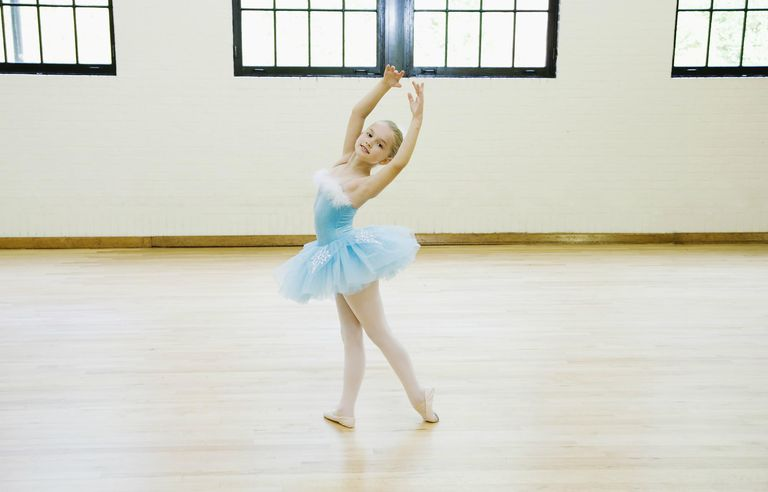 A young ballerina dancing in a studio