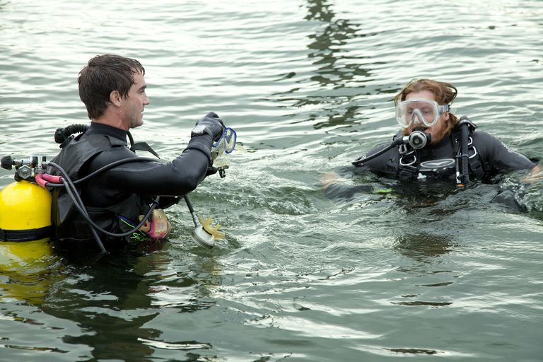 Two scuba divers above water getting ready to go under