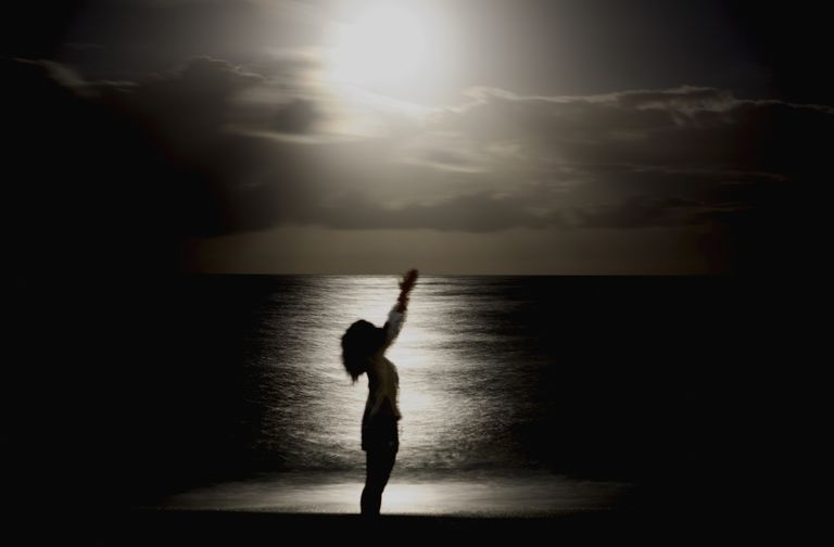 Woman gesturing at the moon in front of the ocean