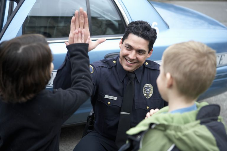 Male police officer high-fiving a young boy